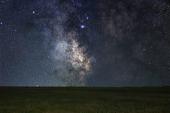Nachtlandschaft mit bunter Milchstraße über Wiese Stockbild