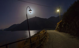 Nachtlandschap met lampen dichtbij de weg, de bergen, het overzees en de maan royalty-vrije stock afbeeldingen