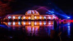 Nachtlaser-Projektion mit farbigen Reflexionen auf dem Wasser Stockbilder