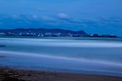 Nachtlichten van de stad op de kust stock afbeelding
