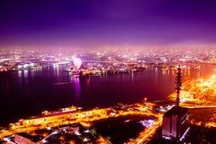 Nachtmeer und Horizont und Stadt und Riesenrad Stockbild