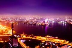 Nachtmeer und Horizont und Stadt und Riesenrad Stockfotografie