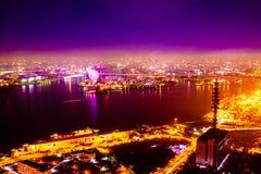 Nachtmeer und Horizont und Stadt und Riesenrad Stockfotos