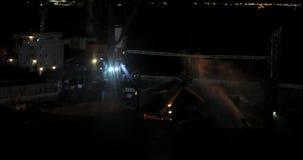 Nachtmeertros van het vrachtschip aan de kade van de steenkoolterminal De havenarbeiders installeren een ladder, nemen meertrosli