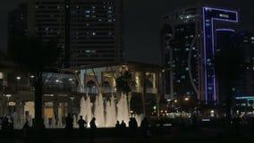 Nachtmening van de stad met een fontein, gebouwen en silhouetten van mensen stock videobeelden