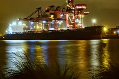 Nachtmening van een brug die bij het leegmaken van een bulk-carrier werken Stock Foto's