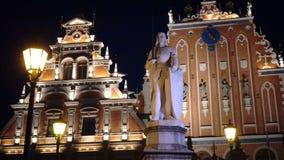Nachtmening van een monument aan Roland bij Stad Hall Square tegen het achtergrondhuis van de Meeëters van Riga Letland stock video