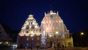 Nachtmening van een monument aan Roland bij Stad Hall Square tegen het achtergrondhuis van de Meeëters van Riga Letland stock footage