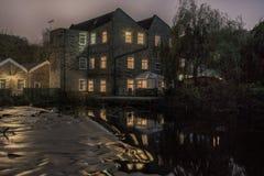 Nachtmening van een oude die molen in de rivier wordt weerspiegeld stock fotografie