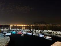 Nachtmening van kleine pijler met gekleurde boten op stadslichten Stock Foto's
