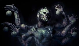 Nachtmerrie, mens in modder met zes wapens stock fotografie