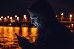Nachtporträt im Freien des jungen Mannes, der Handy verwendet Stockfotos