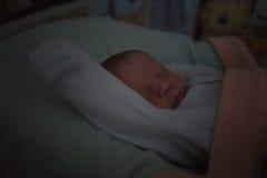 Nachtportret van het slapen van weinig babyjongen, laag licht Stock Foto