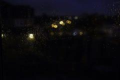 Nachtregentropfen, die auf das Fenster fließen Lizenzfreie Stockbilder