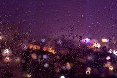 Nachtregnerische Tropfen auf einer Fensterscheibe Stockfotos