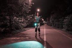 Nachtrollschuhlaufen von eoung tragen Mädchen auf einer Straße zur Schau Lizenzfreie Stockfotos