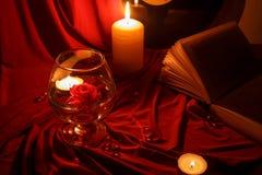 Nachtrotes Stillleben mit Kerzen, einer Rose, einem Buch und einer Aufzeichnung Lizenzfreie Stockbilder