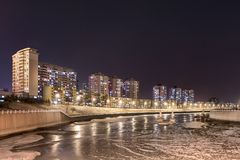 Nachtscène met flatgebouwen dichtbij bevroren kanaal, Tchang-tchoun, China stock fotografie