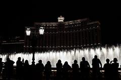 Nachtscène met silhouetten van mensen die de Bellagio fonteinen bewonderen stock afbeeldingen