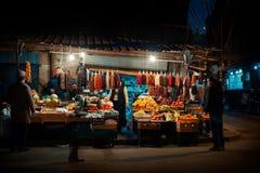 Nachtscène op de straten van Tbilisi, Georgië Straatverkopers rond hoek die traditionele Georgische producten met klanten verkope royalty-vrije stock fotografie
