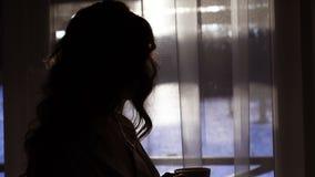 Nachtschattenbild der Frau eine Schale des Getränkes nahe Fenster 4k trinkend stock footage