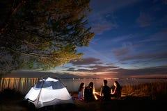 Nachtsommer, der auf Ufer kampiert Gruppe junge Touristen um Lagerfeuer nahe Zelt unter Abendhimmel Lizenzfreies Stockbild