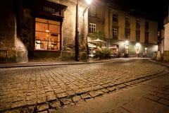 Nachtstad met cobble steen rond weg en bars en koffie Stock Afbeeldingen