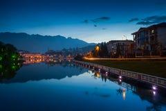 Nachtstadt-Landschaftsansicht mit Gebirgshintergrund und Reflexion des bewölkten Himmels auf Wasser lizenzfreie stockfotos