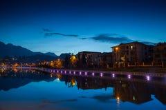Nachtstadt-Landschaftsansicht mit Gebirgshintergrund und Reflexion des bewölkten Himmels auf Wasser stockfoto