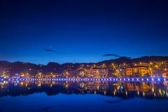 Nachtstadt-Landschaftsansicht mit Gebirgshintergrund und Reflexion des bewölkten Himmels auf Wasser lizenzfreie stockbilder