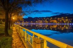 Nachtstadt-Landschaftsansicht mit Gebirgshintergrund und Reflexion des bewölkten Himmels auf Wasser stockfotografie