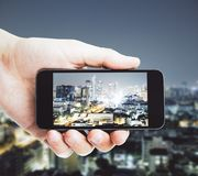 Nachtstadtbild mit Mobiltelefon Stockbild