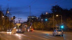 Nachtstadtverkehrsbustram und -autos in der europäischen Stadt