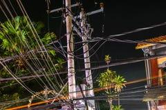 Nachtstraßenansicht des Bündels Drähte angeschlossen auf den Säulen in Bali lizenzfreies stockfoto