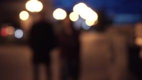 Nachtstraat en silhouetten van mensen, vage achtergrond blur Paar die in de stad bij nacht lopen stock video