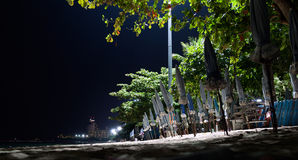 Nachtstrand mit gefalteten Regenschirmen in Folge Sonnenschutz in der Dunkelheit Lizenzfreie Stockfotografie