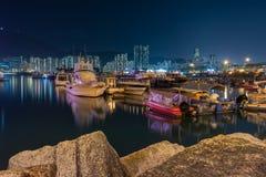 Nachtszene des Fischerdorfes eine kleine Gemeinschaft mit Fischerbooten und Nachtstadtbild an der Lei Yue Mun-Wasserbucht stockbilder