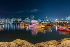 Nachtszene des Fischerdorfes eine kleine Gemeinschaft mit Fischerbooten und Nachtstadtbild an der Lei Yue Mun-Wasserbucht lizenzfreie stockfotografie