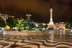 Nachtszene von Rossio-Quadrat, Lissabon, Portugal mit einem seiner dekorativen Brunnen und der Spalte von Pedro IV stockbild