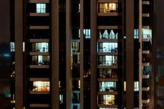 Nachtszene - Vorderansicht des hohen Gebäudes mit Fenstern von Wohnungen, in denen Licht brennt Lizenzfreie Stockfotos