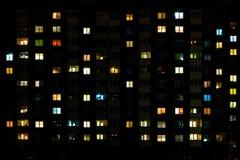 Nachttijdspanne van Licht in de vensters van een gebouw met meerdere verdiepingen Het leven in een grote stad stock foto's