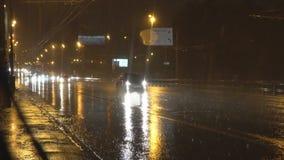 Nachtverkeer op de stadsweg tijdens een zware stortbui stock footage