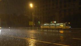 Nachtverkeer op de stadsweg tijdens een zware stortbui stock video