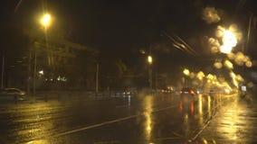 Nachtverkeer op de stadsweg tijdens een zware stortbui stock videobeelden