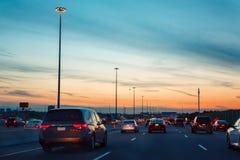 Nachtverkehr, Autos auf Landstraßenstraße auf Sonnenuntergangabendnacht in der beschäftigten Stadt Stockfotografie