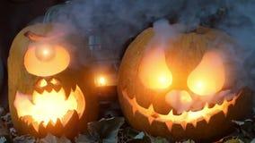 Nachtvideo voor Halloween Twee vreselijke pompoenen tegen droge bladeren en een olielamp met rook in de avond stock videobeelden