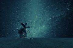 Nachtweinlese-Landschaft mit alter Windmühle und Sternen Stockfotos