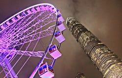 Nachtzeit Ferris Wheel und Wolkenkratzer in Hong Kong Stockfotografie