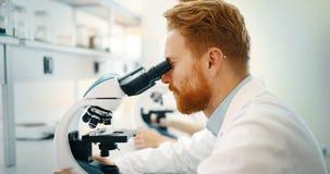 Nachwuchswissenschaftler, der durch Mikroskop im Labor schaut stockfotografie