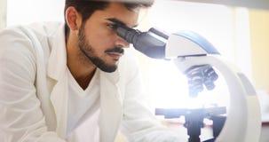 Nachwuchswissenschaftler, der durch Mikroskop im Labor schaut lizenzfreie stockfotos